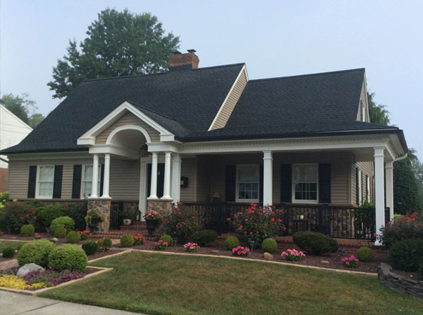 vinyl siding on home with large flower bed