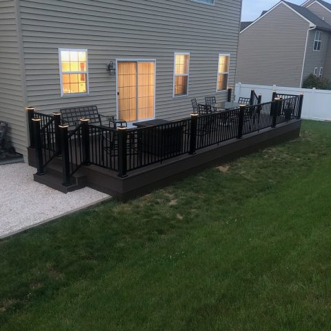 ground level backyard deck in front of green grass